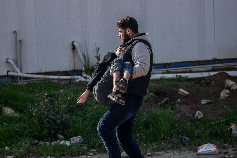 """TOPSHOT - A man carries an injured man after a rocket hit a road in the Reyhanli district in Hatay province, near the Turkey-Syria border, on January 31, 2018. A 17-year-old girl was killed in a Turkish border town on January 31 by rockets launched from Syria, officials said, as Turkey presses its offensive against a Syrian Kurdish militia. Another individual was also hurt after two rockets hit Reyhanli in Hatay province from northern Syria, the district mayor Huseyin Sanverdi said in a statement, and at least one new rocket hit a street not far a few hours later in the centre of Reyhanli, according to an AFP at the scene. Ankara began a cross-border operation dubbed """"Olive Branch"""" supporting Syrian rebels with air strikes and ground troops in northern Syria against the People's Protection Units (YPG) militia and its western enclave of Afrin on January 20. / AFP PHOTO / OZAN KOSE"""