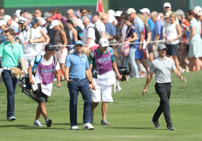 DUBAI, UNITED ARAB EMIRATES - JANUARY 25:  Rory McIlroy of Northern Ireland and Sergio Garcia walk down the fairway on the par 4, ninth hole followed by large crowds during the first round of the Omega Dubai Desert Classic on the Majlis Course at Emirates Golf Club on January 25, 2018 in Dubai, United Arab Emirates.  (Photo by David Cannon/Getty Images)