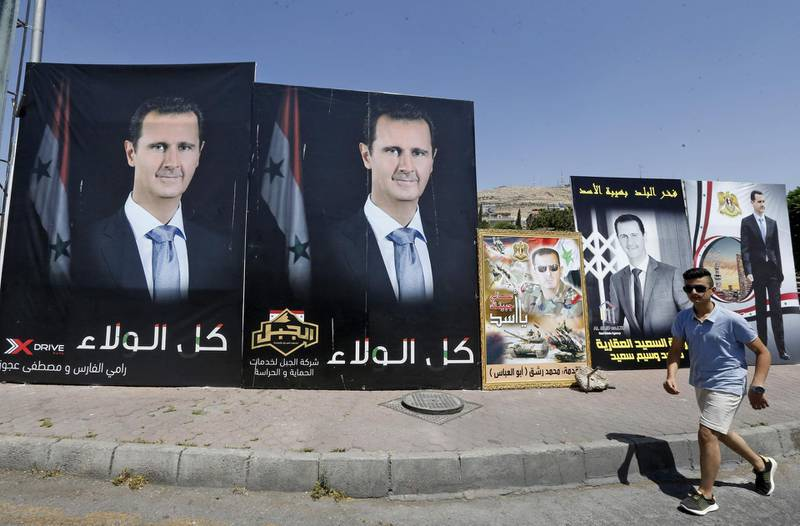A man walks past a poster of President Bashar al-Assad, a candidate for the Presidential election, in the Syrian capital Damascus on May 17, 2021. A Syrian former minister and a member of the Damascus-tolerated opposition will face Bashar al-Assad in this month's presidential election, the constitutional court said. The Assad-appointed body approved only three out of 51 applications to stand in the May 26 ballot, among them the 55-year-old president himself, widely expected to win a fourth mandate. / AFP / LOUAI BESHARA