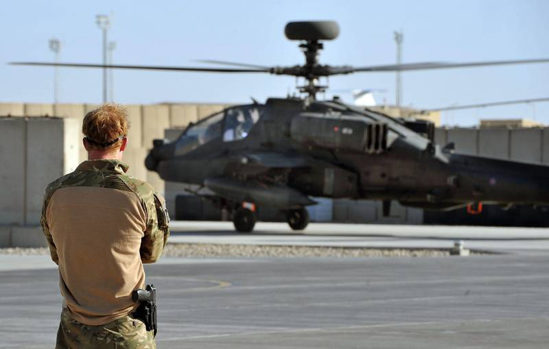 epa03549746 A picture dated 03 November 2012 shows Britain's Prince Harry or just plain Captain Wales as he is known in the British Army, watching the return from a mission, of an Apache Helicopter at the British controlled flight-line in Camp Bastion, southern Afghanistan, where he served as an Apache Helicopter Pilot/Gunner with 662 Sqd Army Air Corps, from September 2012 for four months until January 2013. Prince Harry ended his five-month deployment in Afghanistan on 21 January 2013 with an admission during a BBC interview that he shot at Taliban insurgents as a co-pilot gunner in an Apache attack helicopter. He remarked: 'Take a life to save a life'.  EPA/JOHN STILLWELL / PA WIRE / POOL UK AND IRELAND OUT *** Local Caption ***  03549746.jpg