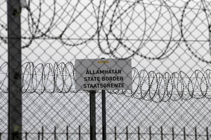 """FILE - In this file photo dated Monday, April 8, 2019, a sign reading: """"State Border"""" is attached to a fence at Hungary's border with Serbia near the village Asotthalom, Hungary.  The European Union's border control agency Frontex, said Wednesday Jan. 27, 2021, it is suspending operations in Hungary after the government in Budapest did not comply with a ruling by Europe's highest court on the rights of asylum-seekers. (AP Photo/Darko Vojinovic, FILE)"""