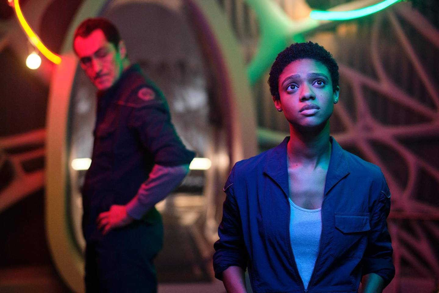 """This image released by Netflix shows Demián Bichir, left, and Tiffany Boone in a scene from """"The Midnight Sky."""" (Philippe Antonello/Netflix via AP)"""