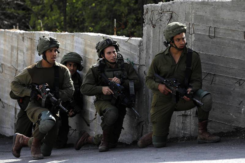 epa06574710 Israeli army take position during clashes with Palestinian stone throwers in the West Bank city of Hebron, 02 March 2018.  EPA/ABED AL HASHLAMOUN