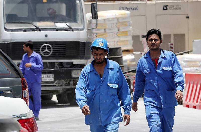 DUBAI , UNITED ARAB EMIRATES , JUNE 14 – 2018 :- Labourers going to their staff bus after the midday break at one of the construction site in Al Garhoud area in Dubai. ( Pawan Singh / The National )  For News. Story by Ramola