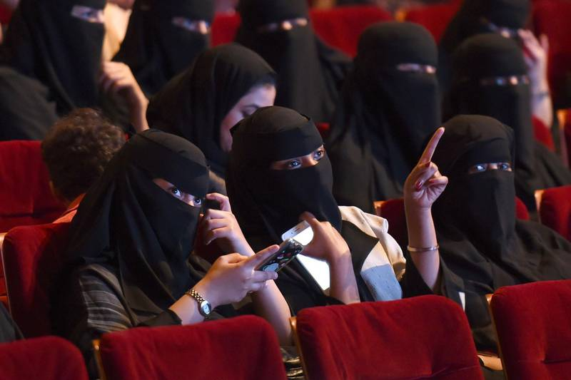 """(FILES) This file photo taken on October 20, 2017 shows Saudi women attending the """"Short Film Competition 2"""" festival at King Fahad Culture Center in Riyadh. Saudi Arabia on Monday announced a lifting of the kingdom's decades-long ban on cinemas, a landmark decision part of a series of social reforms ushered in by the powerful crown prince.  / AFP PHOTO / FAYEZ NURELDINE"""