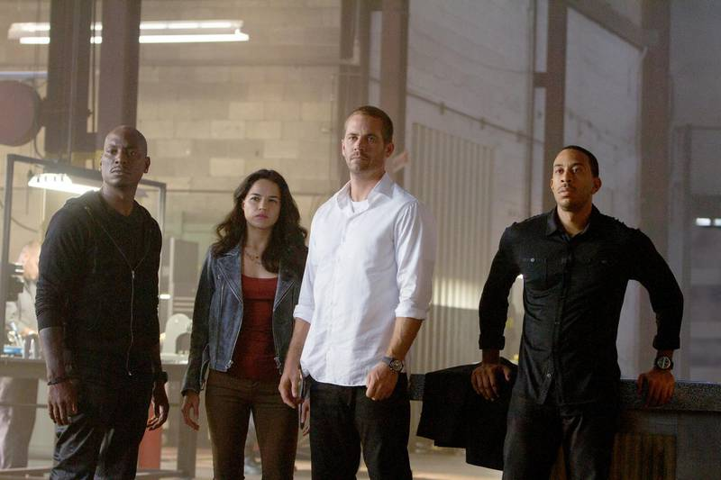 """A handot photo of (L to R) Roman (TYRESE GIBSON), Letty (MICHELLE RODRIGUEZ), Brian (PAUL WALKER) and Tej (CHRIS """"LUDACRIS"""" BRIDGES) are back for """"Furious 7"""". Continuing the global exploits in the unstoppable franchise built on speed, James Wan directs this chapter of the hugely successful series. (Scott Garfield / Universal Pictures)"""