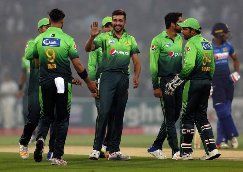 Pakistan's Mohammad Amir, center, celebrates with teammates after taking the wicket of Sri Lankan batsman Dilshan Munaweera during their third Twenty20 international match at the Gaddafi stadium in Lahore, Pakistan, Sunday, Oct. 29, 2017. (AP Photo/K.M. Chaudary)