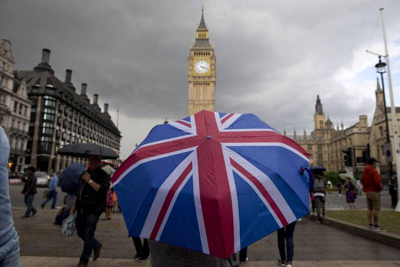 (FILES) In this file photo taken on June 25, 2016 A pedestrian shelters from the rain beneath a Union flag themed umbrella as they walk near the Big Ben clock face and the Elizabeth Tower at the Houses of Parliament in central London on June 25, 2016, following the pro-Brexit result of the UK's EU referendum vote. The European Union and Britain could agree the terms of a post-Brexit trade deal within hours, European sources told AFP on December 23, 2020, as negotiations continued. / AFP / JUSTIN TALLIS