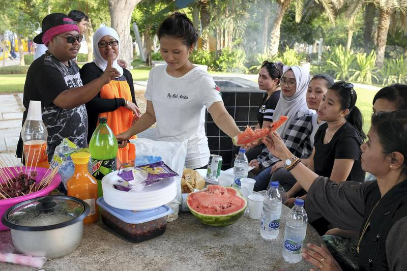DUBAI, UNITED ARAB EMIRATES. 21 AUGUST 2018. Residents of Dubai enjoy the Eid break. Riana Rabox (Indonesia) hands out watermelon out to her friends during a barbeque in Zabeel parkt. (Photo: Antonie Robertson/The National) Journalist: None. Section: National.
