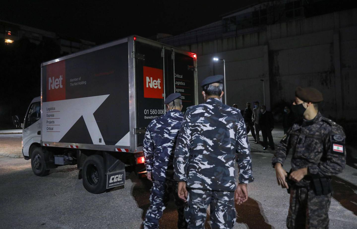 Members of Lebanese security forces stand next to a truck transporting boxes of the first shipment of the COVID-19 Pfizer-BioNTech vaccine upon arrival to the Rafic Hariri University Hospital in the capital Beirut, on February 13, 2021. Lebanon received its first vaccines against the coronavirus, a day before an inoculation drive kicks off in the crisis-hit Mediterranean country. / AFP / ANWAR AMRO