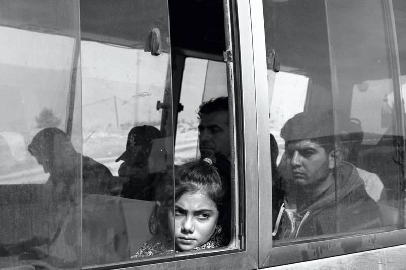 IRAQ. Sahela Border Crossing. November 1, 2019. Newly arrived Syrian-Kurdish refugees aboard a bus operated by the International Organization of Migration (IOM). Buses transport the newly arrived refugees from the Sahela Iraq-Syria border crossing in Iraqi-Kurdistan to the Bardarash refugee camp in Dohuk Province, Iraqi-Kurdistan.