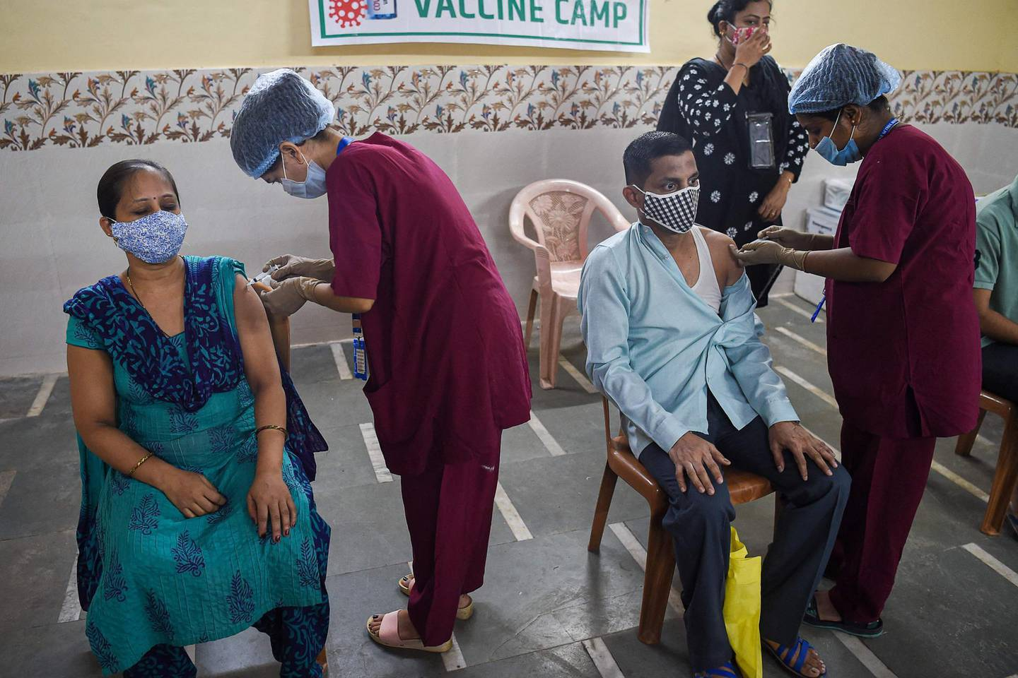 Residents get inoculated with a dose of the Covishield, AstraZeneca-Oxford's Covid-19 coronavirus vaccine, at a vaccination centre in the Dharavi slums in Mumbai on June 29, 2021. / AFP / Punit PARANJPE