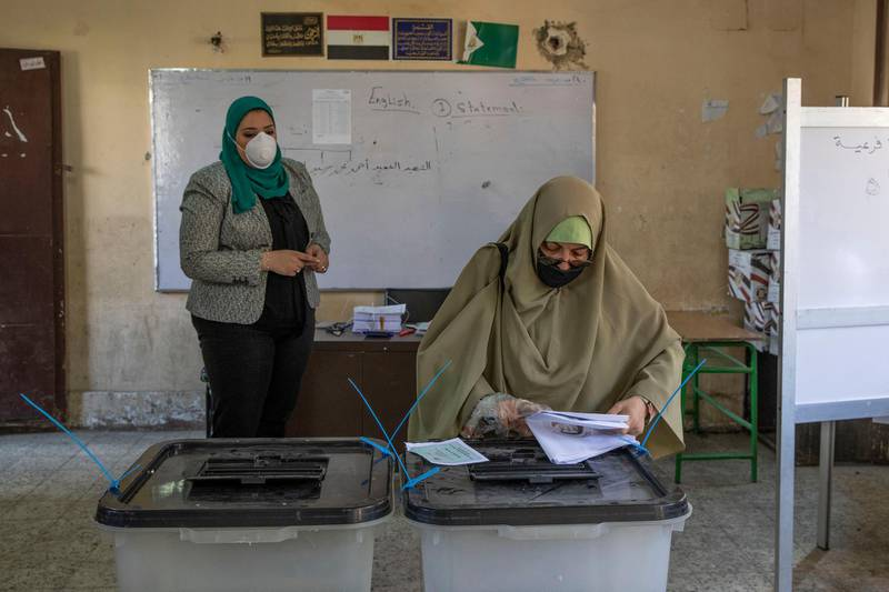 A woman casts her ballot on the first day of the Senate elections inside a polling station in Cairo, Egypt, Tuesday, Aug. 11, 2020. Egyptians started voting on Tuesday for the Senate, the upper chamber of parliament that was revived as part of constitutional amendments approved in a referendum last year — an election that comes as the country faces an uptick in daily numbers of new coronavirus cases. (AP Photo/Nariman El-Mofty)