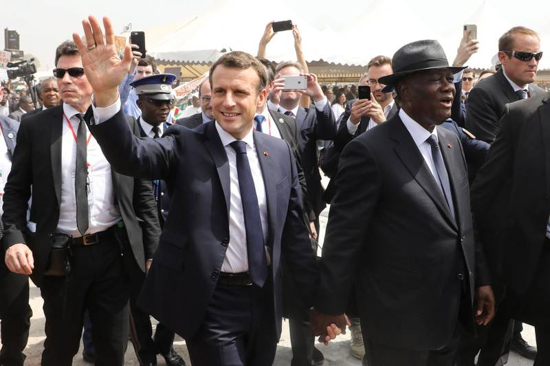 TOPSHOT - French President Emmanuel Macron (L) and Ivorian President Alassane Ouattara (R) arrive to attend a ceremony to lay the first brick of the future Bouake market, which had burnt down 20 years prior, on December 22, 2019, in Bouake, as part of a three-day visit to West Africa. / AFP / Ludovic MARIN