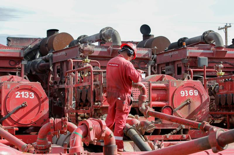 FILE - In a Monday, June 26, 2017, file photo, a Halliburton employee works near rows of hydraulic fracturing pumping units at a three pad site in Midland, Texas. Halliburton Co. reports earnings, Monday, Jan. 22, 2018. (Steve Gonzales//Houston Chronicle via AP, File)