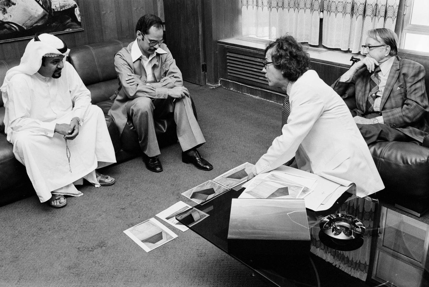 Christo, in the white suit, explaining the preliminary engineering concept for The Mastaba to officials of the Ministry of Construction. The man seated next to the dishdasha guy is Azmi Abu Taleb, Municipal Town Planning Architect.) Photo: Wolfgang Volz, ©Christo.