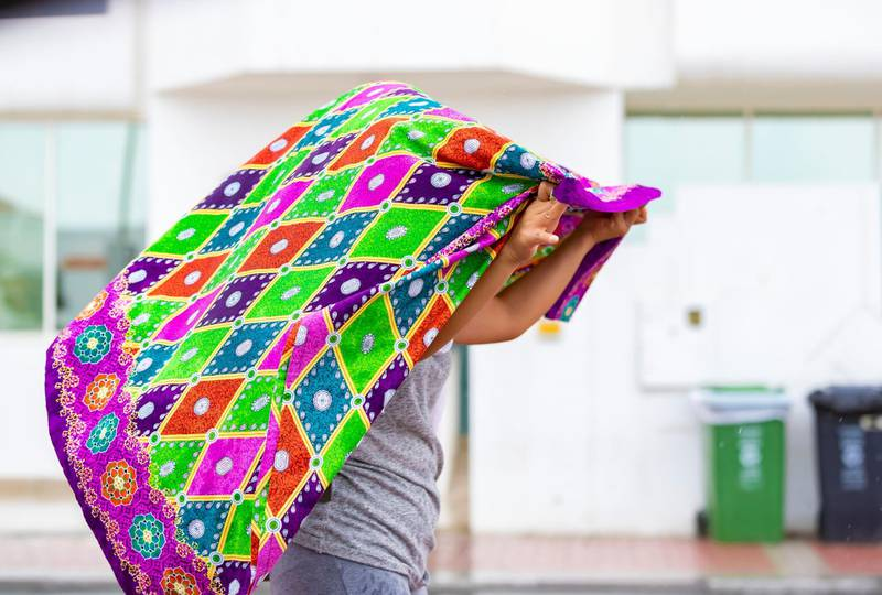 Dubai, United Arab Emirates - Reporter: N/A: Weather. A lady covers her hair as the rain comes down in Dubai. Saturday, March 21st, 2020. Jumeirah, Dubai. Chris Whiteoak / The National