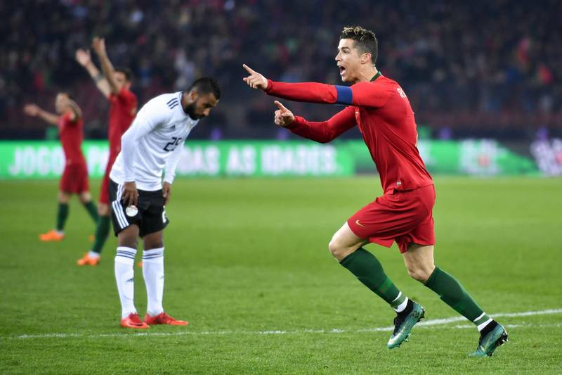 Portugal's forward Cristiano Ronaldo (R) reacts after scoring a goal during the international friendly football match between Portugal and Egypt at Letzigrund stadium in Zurich on March 23, 2018. / AFP PHOTO / Fabrice COFFRINI