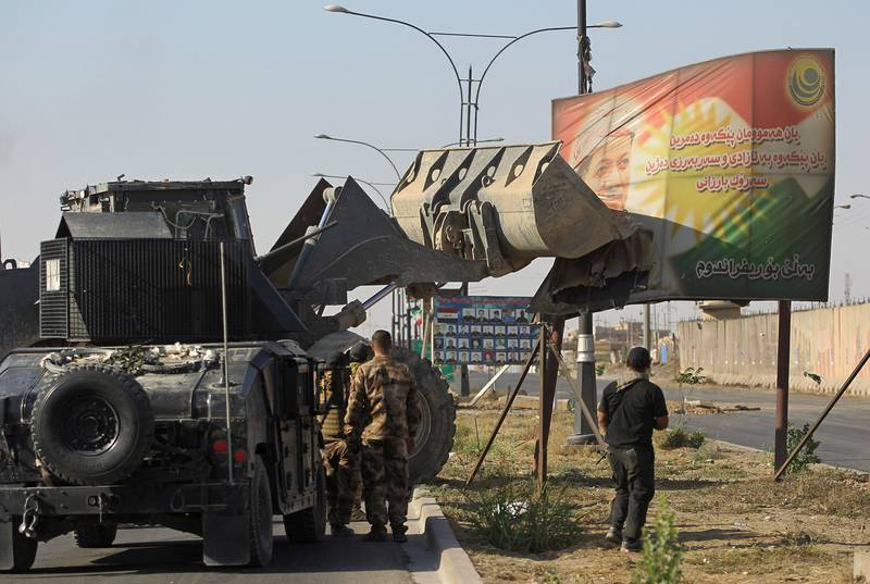 Iraqi forces use a tractor to damage a poster of Iraqi Kurdish president Massud Barzani on the southern outskirts of Kirkuk on October 16, 2017.  Thousands of residents fled Kurdish districts of Kirkuk for fear of clashes after Iraqi military forces launched operations against Kurdish fighters near the northern city, an AFP journalist said. / AFP PHOTO / AHMAD AL-RUBAYE
