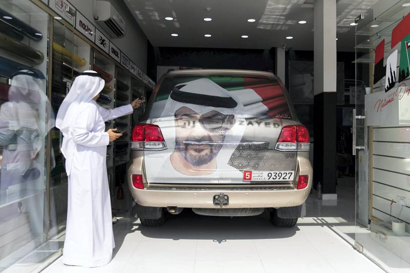 ABU DHABI, UNITED ARAB EMIRATES - NOVEMBER 27, 2018. Rashid Al Muhairbi, who's birthday falls on UAE National's day, decorates his car at Grand Plus Auto Accessories. Car accessory shops in Mussafah are keeping busy as motorists rush to dress up their vehicles ahead of the UAE's 47th National Day.(Photo by Reem Mohammed/The National)Reporter:  HANEEN DAJANISection:  NA