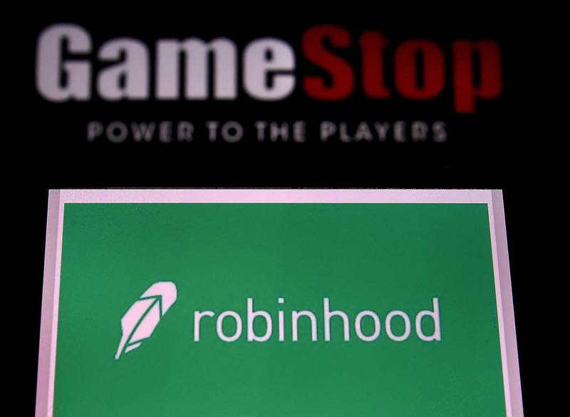 (FILES) In this file photo illustration taken on January 28, 2021, shows the logos of video grame retail store GameStop and trading application Robinhood in a computer and on a mobile phone in Arlington, Virginia. Key players involved in the trading frenzy centered on GameStop shares told skeptical US lawmakers on February 18, 2021 that their actions were above board and in line with ordinary stockmarket business. Founders of free stock-trading app Robinhood and online forum Reddit were among those to testify at a House of Representatives financial services committee hearing.  / AFP / Olivier DOULIERY