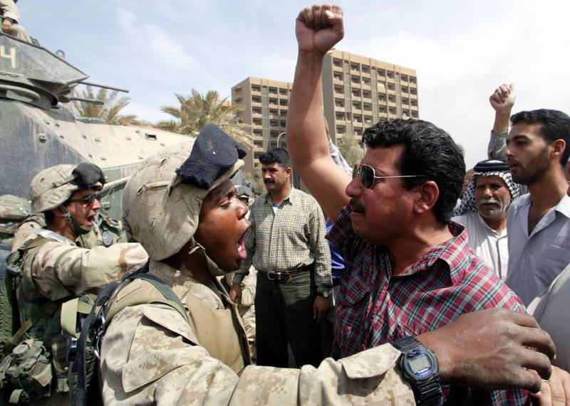 U.S. soldiers attempt to calm Iraqi's during a rally demanding the reinstatement of law and order, in the centre of Baghdad, April 12, 2003. U.S. and British troops struggled to restore order to Iraqi cities on Saturday as looters rampaged through ministries, schools and shops in a frenzy of plunder and arson. U.S. soldiers with tanks secured the last known Baghdad stronghold of foreign fighters loyal to Saddam Hussein. REUTERS/Gleb Garanich   PP03040037  GG/JV