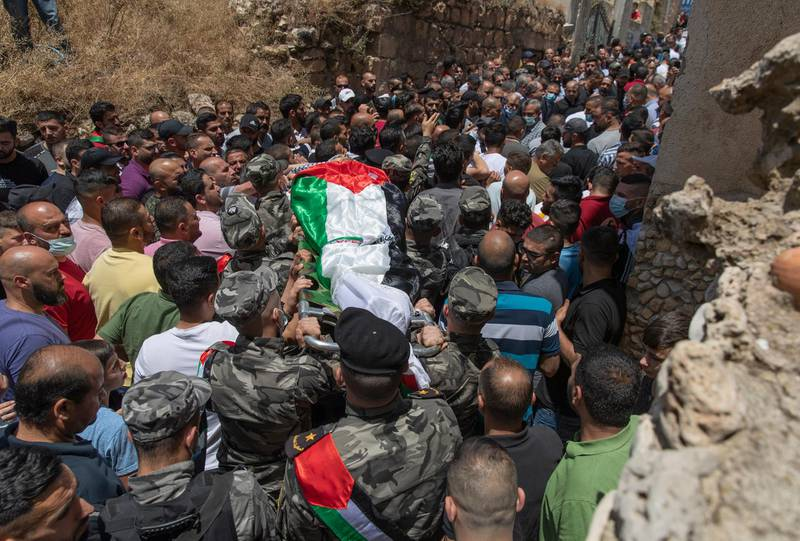 Palestinian security officer carry the body of Mohammad Daraghmeh out of the family house during his funeral in the West Bank village of Lubban, near Nablus, Wednesday, May 12, 2021. Israeli soldiers opened fire yesterday at a Palestinian vehicle at an army checkpoint north of the West Bank, killing Daraghmeh, a passenger, and critically wounding another, the Palestinian health ministry said. (AP Photo/Nasser Nasser)
