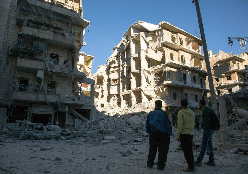 Syrian men look at a heavily damaged building following air strikes on rebel-held eastern areas of Aleppo on September 24, 2016. - Heavy Syrian and Russian air strikes on rebel-held eastern areas of Aleppo city killed at least 25 civilians on Saturday, the Britain-based Syrian Observatory for Human Rights said, overwhelming doctors and rescue workers. (Photo by KARAM AL-MASRI / AFP)