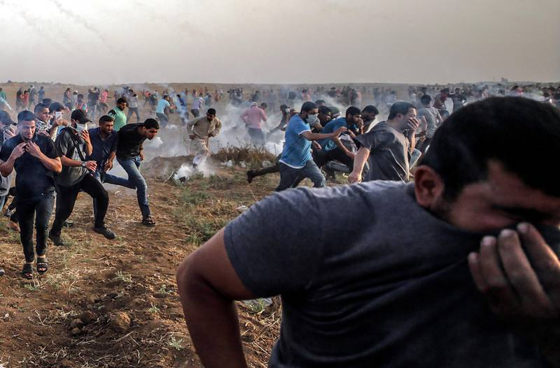 epaselect epa06763718 Palestinians protesters run for cover from Israeli tear-gas during the clashes near the border between Israel and Gaza Strip, eastern Gaza City on, 25 May 2018. More than 120 Palestinians protesters have been injured during the clashes near the border with Israel, Protesters plan to call for the rights of Palestinian refugees across the Middle East to return to homes they fled in the war surrounding the 1948 creation of Israel.  EPA/MOHAMMED SABER