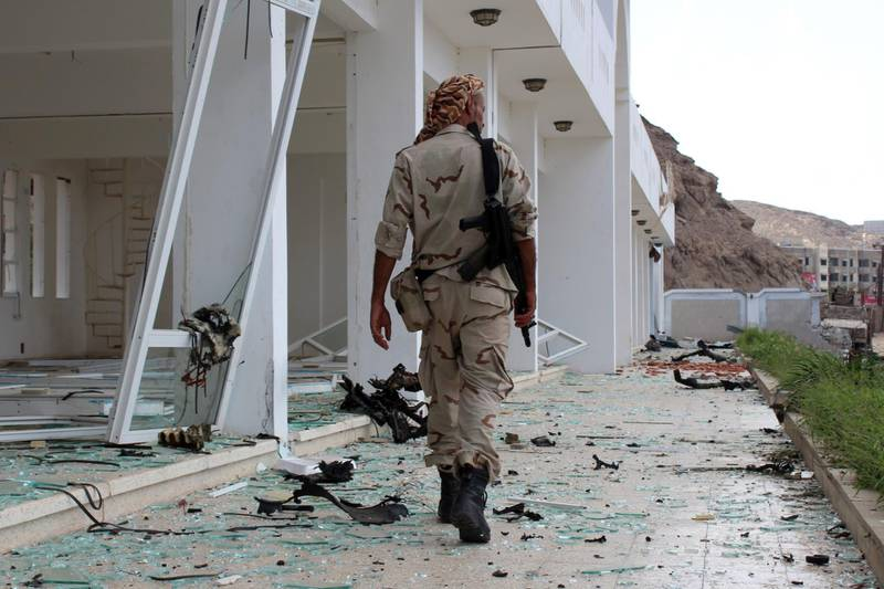 A fighter from the separatist Southern Transitional Council gather on February 25, 2018, at the site of two suicide car bombings that targeted the headquarters of an anti-terror unit the day before, in the southern Yemeni port of Aden. Five people, including security officers and a child, died in the blasts at the headquarters of an anti-terror unit in the Tawahi district, Aden security chief General Shallal al-Shae said.  / AFP PHOTO / SALEH AL-OBEIDI