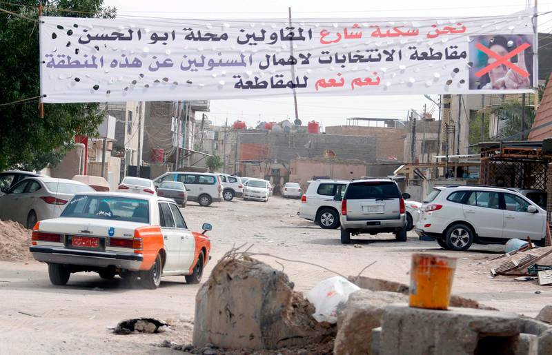 A banner calling voters to boycott the parliamentary elections in Iraq hangs in a neighbourhood in the southern city of Basra on May 8, 2018 as residents feel they are neglected by the federal government.  Iraqi goes to the poll on May 12. / AFP PHOTO / HAIDAR MOHAMMED ALI
