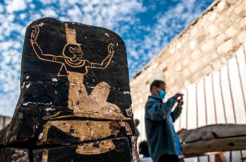 A visitor takes pictures next to an unearthed wooden coffin during the official announcement of the discovery by an Egyptian archaeological mission of a new trove of treasures at Egypt's Saqqara necropolis south of Cairo, on January 17, 2021. The discovery at the necropolis which lies 30kms south of the Egyptian capital, includes the funerary temple of Queen Naert, wife of King Teti, as well as burial shafts, coffins, and mummies dating back to the New Kingdom, dating back to more than 2500 years. / AFP / Khaled DESOUKI