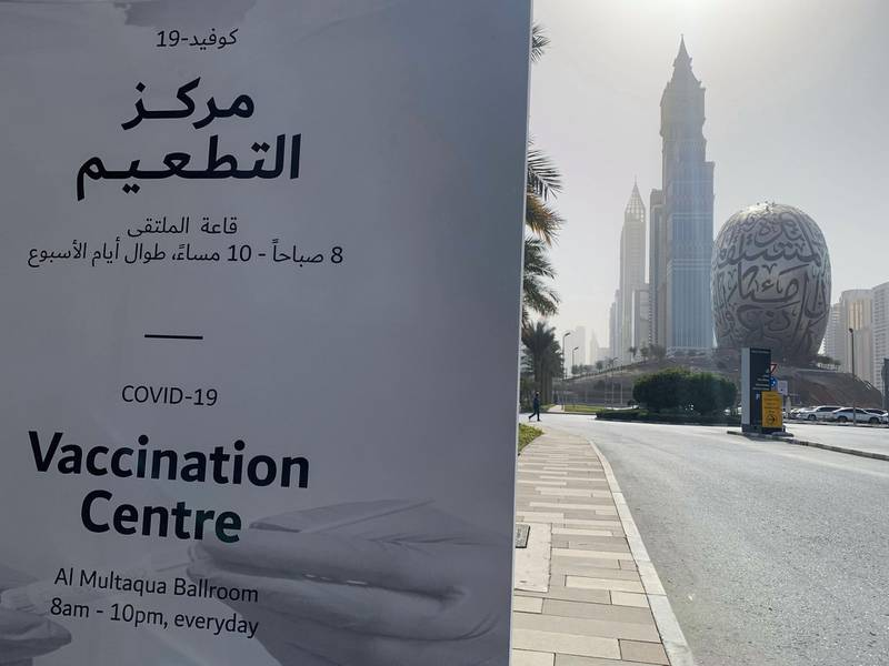 An advertisement placard informs the public of the location of a designated COVID-19 vaccination center at Dubai's financial center district, in the United Arab Emirates, on January 24, 2021. The emirate of Dubai has said it was slowing down its rollout of the Pfizer-BioNTech coronavirus vaccine due to a temporary delay in global deliveries. / AFP / Giuseppe CACACE
