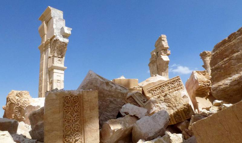 """A general view taken on March 27, 2016 shows part of the remains of Arch of Triumph, also called the Monumental Arch of Palmyra, that was destroyed by Islamic State (IS) group jihadists in October 2015 in the ancient Syrian city of Palmyra, after government troops recaptured the UNESCO world heritage site from the Islamic State (IS) group. - President Bashar al-Assad hailed the victory as an """"important achievement"""" as his Russian counterpart and key backer Vladimir Putin congratulated Damascus for retaking the UNESCO world heritage site. (Photo by Maher AL MOUNES / AFP)"""