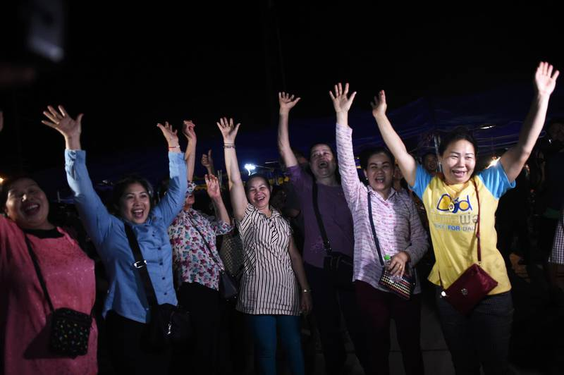 TOPSHOT - Volunteers celebrate at a makeshift press centre in Mae Sai district of Chiang Rai province on July 10, 2018, after the twelve boys and their football coach were rescued. The final five members of a young football team were rescued from a flooded Thai cave on July 10, after spending 18 harrowing days trapped deep inside, completing an astonishing against-the-odds rescue mission that captivated the world. / AFP / Ye Aung THU