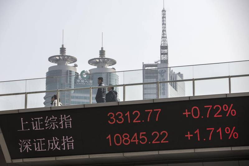 People walk along an elevated walkway as an electronic ticker displays the figures of the ShanghaiCompositeIndex, top, and the SZSE Component Index in the Lujiazui Financial District in Shanghai, China, on Monday, Feb. 26, 2018. Xi Jinping'sdecision to cast aside China's presidential term limits is stoking concern he also intends to shun international rules on trade and finance, even as he champions them on the world stage. Photographer: Qilai Shen/Bloomberg