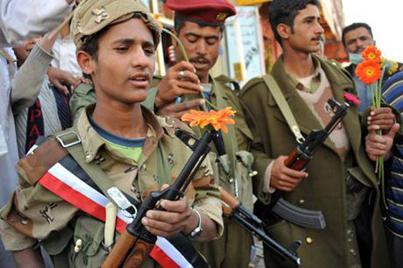 epa02649046 Yemeni army soldiers hold flowers they received from anti-government protesters demanding the ouster of Yemeni President Ali Abdullah Saleh, during protest in the capital Sanaía, Yemen, 23 March 2011. According to media sources, Yemen's parliament on 23 March voted in support of imposing the emergency law  for 30 days, a motion requested by President Ali Abdullah Saleh in the midst of ongoing anti-government protests. The emergency law suspends the country's constitution, bans protests, and allows for arbitrary arrests and censorship.  EPA/YAHYA ARHAB *** Local Caption ***  02649046.jpg