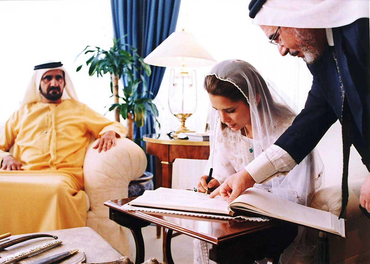Jordan's Princess Haya, King Abdullah II's half-sister, right, signs her wedding register to Dubai's Crown Prince and Defence Minister Mohammed bin Rashed al-Maktoum, who is seen sitting at left, at the Baraka Palace in Amman, Jordan, Saturday April 10, 2004. Princess Haya, 29, is the eldest daughter of Jordan's late King Hussein from his third wife, Alia-Touqan, a Palestinian Jordanian who died in a 1977 helicopter crash. Prince Sheik Mohammed and Princess Haya,  were married Saturday.(AP Photo/Royal Palace)