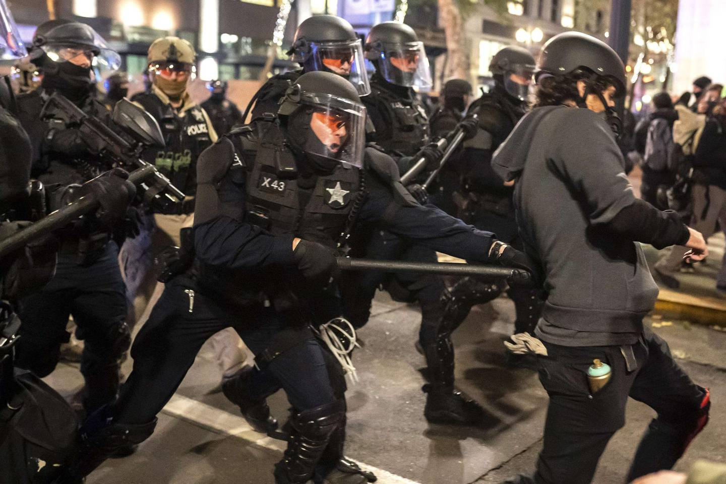 PORTLAND, OR - NOVEMBER 04: An Oregon State Trooper hits a protester with his baton while dispersing a crowd of black bloc protesters on November 4, 2020 in Portland, Oregon. Multiple protests, some peaceful and others violent, broke out in Portland as the presidential election remained undecided.   Nathan Howard/Getty Images/AFP == FOR NEWSPAPERS, INTERNET, TELCOS & TELEVISION USE ONLY ==
