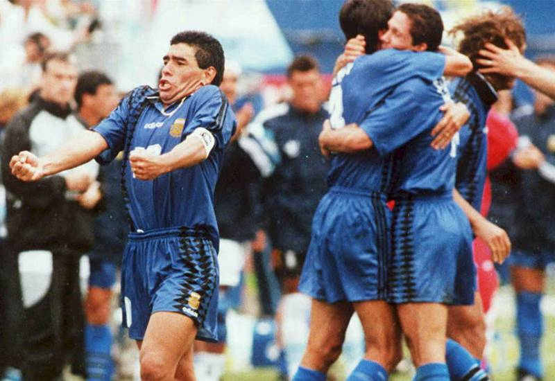 Argentine national soccer team captain, Diego Maradona (L) yells out as he and his teammates (R) celebrate after Argentina scored its second goal against Greece 21 June 1994 at Foxboro Stadium in Foxboro, Massachussetts. Argentian won the game 4-0. (Photo by DANIEL GARCIA / AFP FILES / AFP)