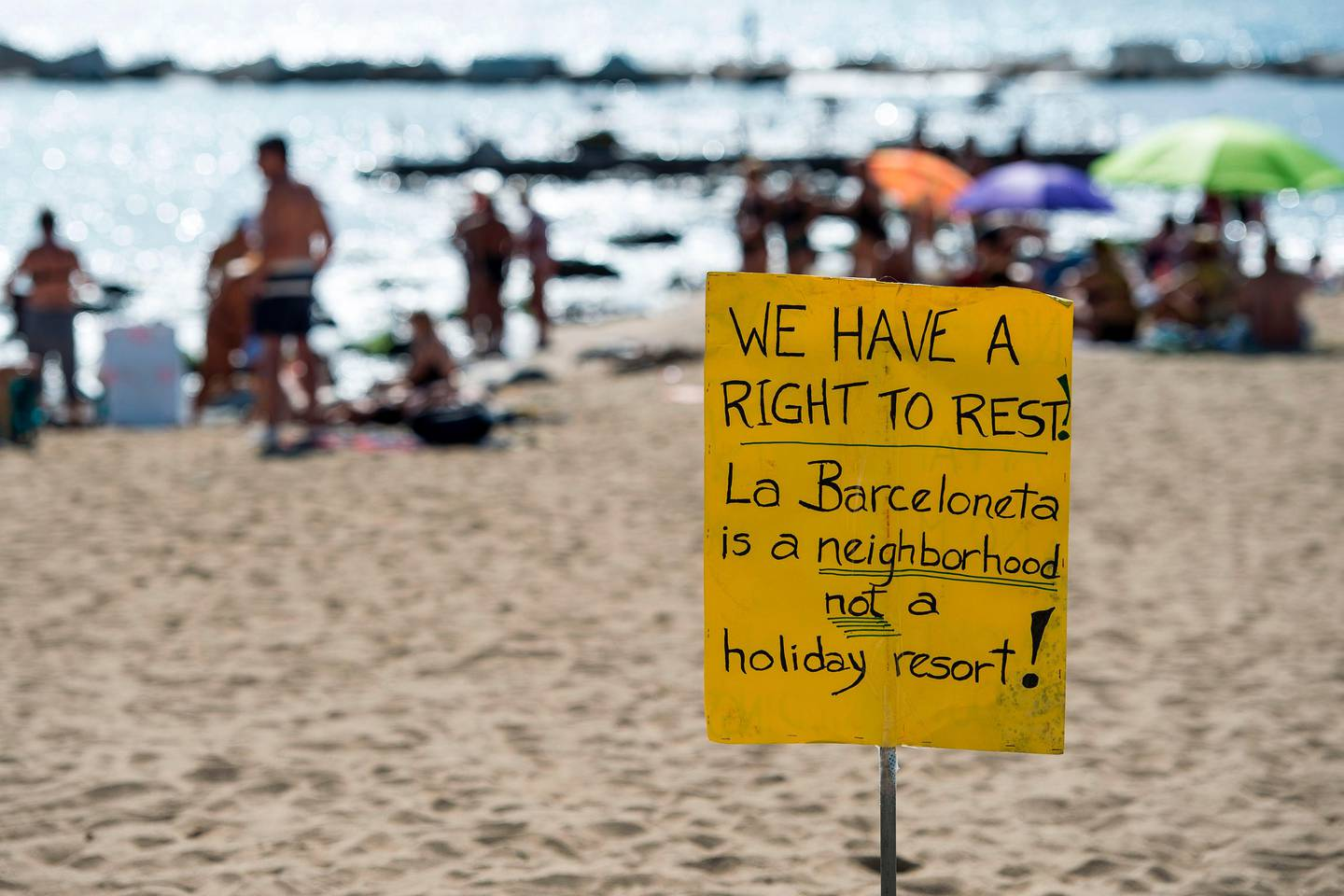 """Picture shows a protest-placard on La Barceloneta beach during a demonstration against """"drunken tourism"""" called by the residents of La Barceloneta neighbourhood in Barcelona, on August 12, 2017.    / AFP PHOTO / Josep LAGO"""