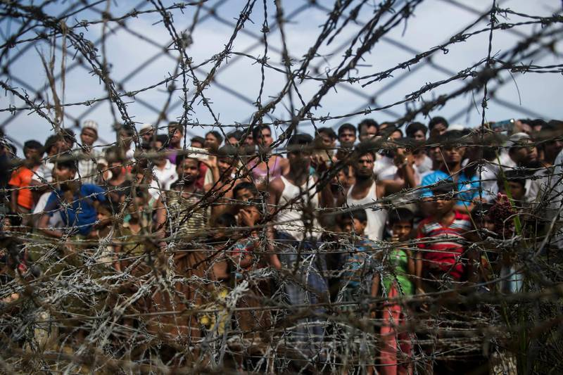 """This picture taken from Maungdaw district, Myanmar's Rakhine state on April 25, 2018 shows Rohingya refugees gathering behind a barbed-wire fence in a temporary settlement setup in a """"no man's land"""" border zone between Myanmar and Bangladesh. A United Nations Security Council delegation which wants to see first-hand the impact of the Rohingya refugee crisis will arrive in Myanmar on April 30 and visit Rakhine state, a senior government official said. Myanmar and Bangladesh signed a repatriation deal for refugees to return in January but so far only one family has returned from a no man's land between the two nations. / AFP PHOTO / Ye Aung THU"""