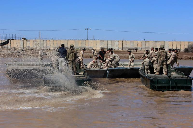 (FILES) In this file photo taken on March 06, 2017 international coalition forces and Iraqi soldiers instal a floating bridge at the Taji camp, north of Baghdad, during a training session. Katyusha rockets targeted an Iraqi airbase north of Baghdad hosting US-led coalition forces, the Iraqi military said on January 14, 2020 in the latest attack on installations where American troops are deployed. The statement from Iraq's military did not say how many rockets had hit Camp Taji but reported that there were no casualties. / AFP / SABAH ARAR