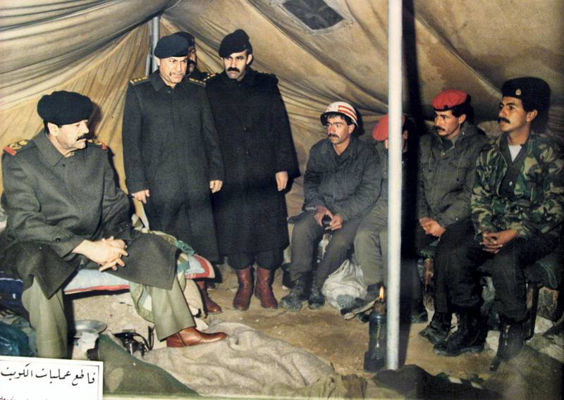 A reproduction of a picture displayed at the Nasr or Victory Museum in Baghdad shows Iraqi President Saddam Hussein (L) visiting Iraqi troops at a military camp in occupied territory in Kuwait after the August 2, 1990 invasion of the Gulf emirate. The Nasr Museum is dedicated to the Iraqi leader and includes painting made of and for him, uniforms and weapons he used during the 1991 Gulf War and official gifts he received during his two-decade reign. The 10th anniversary of the Gulf War, when a US-led international coalition unleashed a war to liberate Kuwait from Iraqi occupation, is coming up 16 January 2001. AFP PHOTO/Karim SAHIB AFP PHOTO AFP/KARIM SAHIB/mro (Photo by AFP)