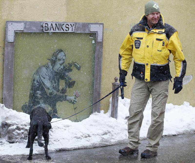 """epa05732385 A policeman and a bomb sniffing dog checks out a snow pile next to a """"Banksy"""" painting along Old Main Street on the first day of the 2017 Sundance Film Festival in Park City, Utah, USA, 19 January 2017. The festival runs from 19 to 29 January.  EPA/GEORGE FREY"""