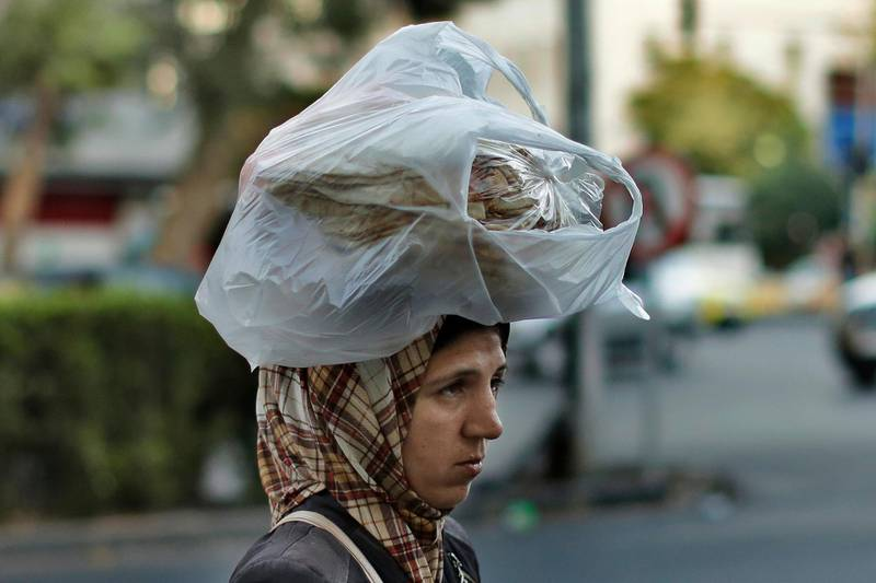 FILE - In this July 24, 2019 file photo, a woman carries bread on her head while she crosses a street in the Syrian capital, Damascus. In Syria nowadays, there is an impending fear that all doors are closing. After nearly a decade of war, the country is crumbling under the weight of years-long western sanctions, government corruption and infighting, a pandemic and an economic downslide made worse by the financial crisis in Lebanon, Syria's main link with the outside world. (AP Photo/Hassan Ammar, File)