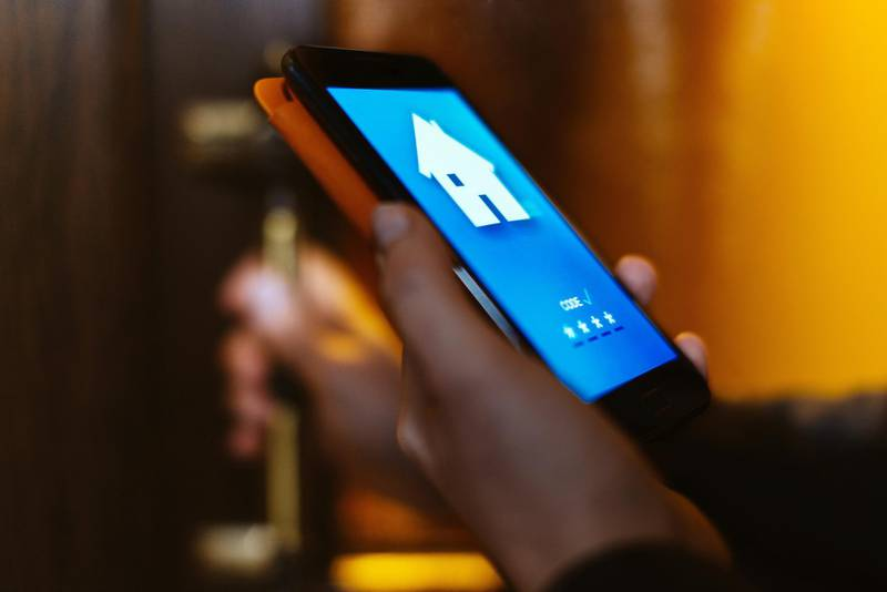 Woman using home app to open the door of her house with her smart phone, close-up.