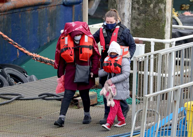 People thought to be migrants are guided after being brought into port by Border Force officers following a small boat incident in the Channel, at Dover southern England, Monday March 8, 2021. (Gareth Fuller/PA via AP)