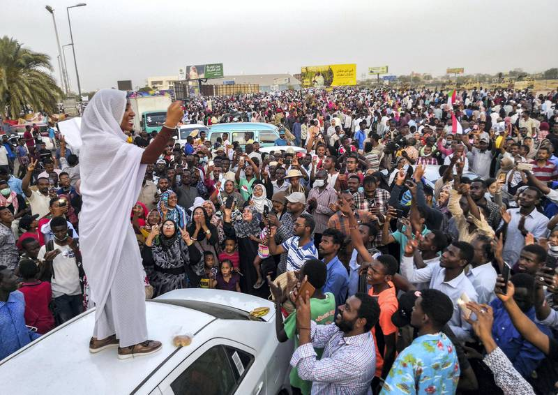 """Alaa Salah, a Sudanese woman propelled to internet fame earlier this week after clips went viral of her leading powerful protest chants against President Omar al-Bashir, addresses protesters during a demonstration in front of the military headquarters in the capital Khartoum on April 10, 2019. - In the clips and photos, the elegant Salah stands atop a car wearing a long white headscarf and skirt as she sings and works the crowd, her golden full-moon earings reflecting light from the fading sunset and a sea of camera phones surrounding her. Dubbed online as """"Kandaka"""", or Nubian queen, she has become a symbol of the protests which she says have traditionally had a female backbone in Sudan. (Photo by - / AFP)"""