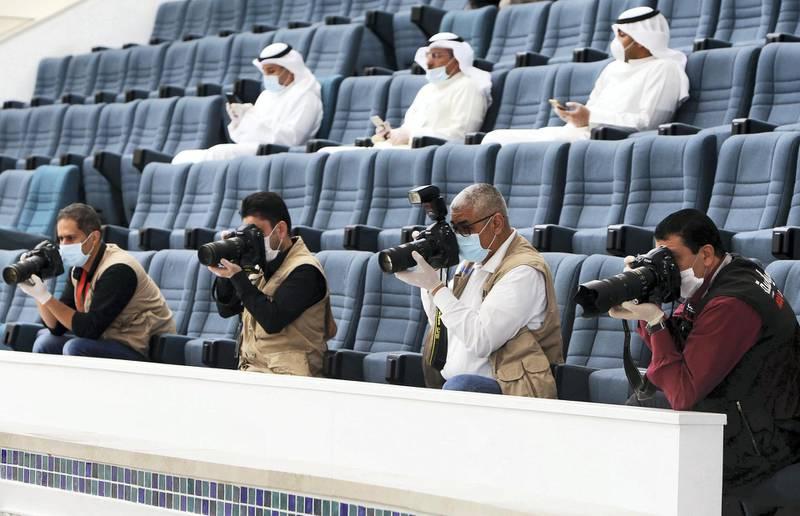 Press photographers wearing protictive masks attend a parliament session at Kuwait's national assembly in Kuwait City on March 24, 2020. (Photo by YASSER AL-ZAYYAT / AFP)